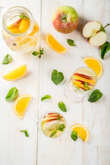 음료와 칵테일. 사과, 오렌지, 민트와 화이트 와인 화이트가 상그리아. 흰색 나무 테이블에 투 수에서 샴페인 안경. 복사 공간 평면도