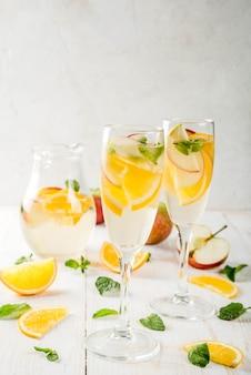 음료와 칵테일. 사과, 오렌지, 민트와 화이트 와인 화이트가 상그리아. 흰색 나무 테이블에 투 수에서 샴페인 안경. 공간 복사