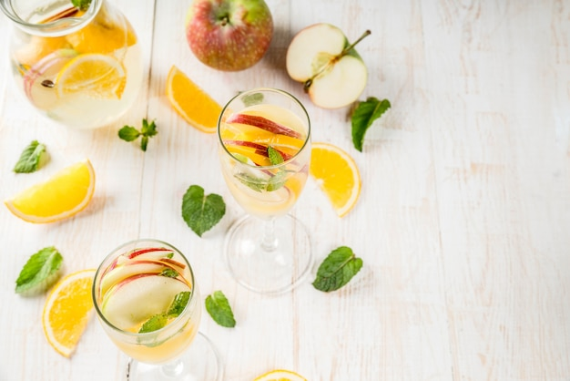 음료와 칵테일. 사과, 오렌지, 민트, 화이트 와인과 함께 하얀 가을 상그리아