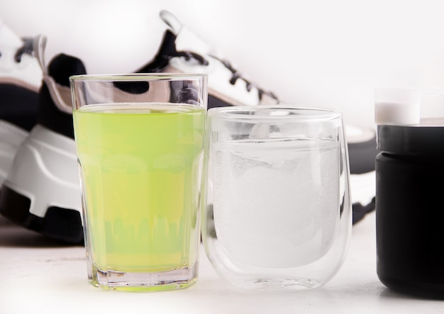 Drinks on the background of sports shoes. the concept of proper nutrition in sports