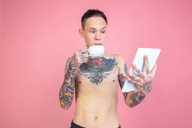 タブレットを使用して、コーヒーを飲みます。ピンクの背景に奇抜な外観を持つ若者の肖像画。