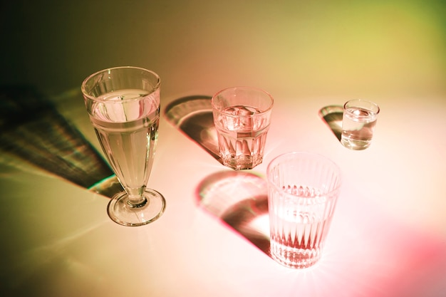 Drinks in the different type of glasses with shadow on colored backdrop