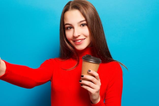 음료, 감정, 사람, 아름다움, 라이프스타일 개념 - 파란색 스튜디오 배경에 빨간 블라우스를 입은 감정적인 행복한 아름다운 여성이 웃고 있는 종이컵, 아침 음식, 셀카 커피 한 잔