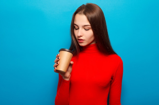 Drinks, emotions, people, beauty, lifestyle concept - emotional happy beautiful woman in red blouse on blue studio background drinking coffee in paper cup smiling, positive, enjoying, morning food