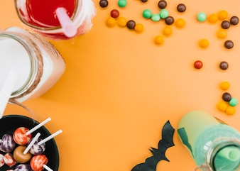 Drinks in bottle and candy on edges and space in center on orange background
