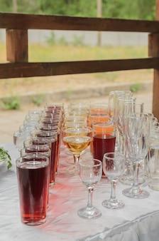 Напитки в чашках и стаканах на столе, фуршет