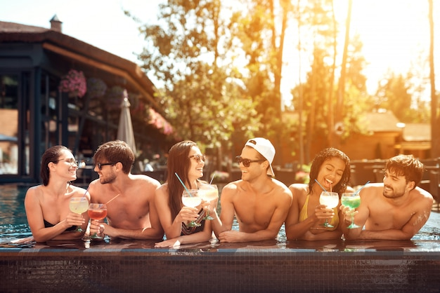 Drinks at poolside. happy friends enoying pool party.