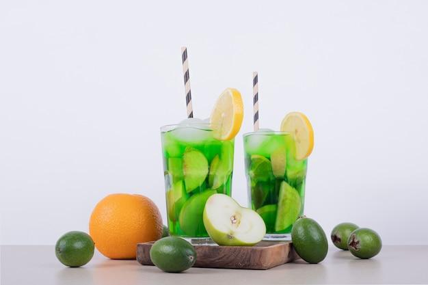 Bevande con mela, feijoa e paglia su bianco