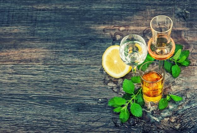 나무 배경에 얼음, 레몬, 민트 잎을 넣은 음료. 빈티지 스타일 톤 그림