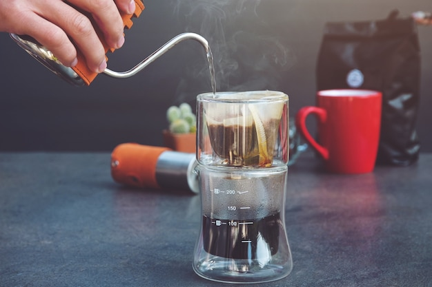 Drip brew coffee caffeine filter flavor mug cup. man spills hot water prepare filtered coffee transparent glass drip maker on table . steam