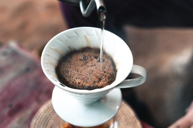 ドリップコーヒー、フィルター付きコーヒーグラウンドに水を注ぐバリスタ、コーヒーを淹れる