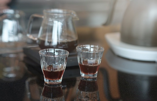 The drip coffee is ready to be served in a cup on the table.