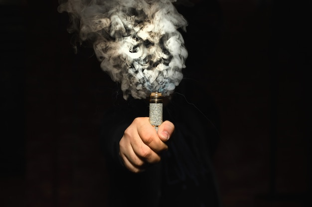 Dripper in one hand making a cloud of fume