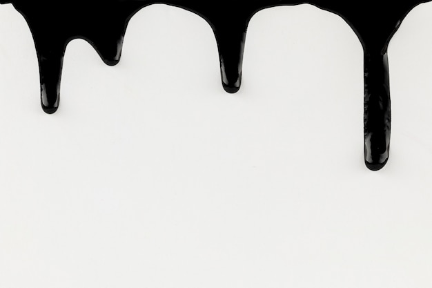 Dripping black paint on white background