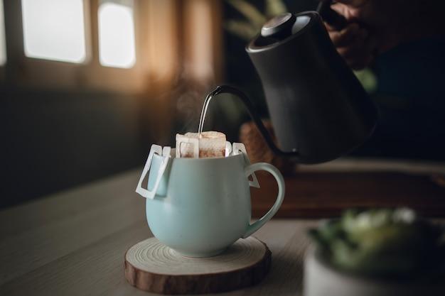 아침에 집에서 떨어지는 커피. 선과 아늑한 생활. 주전자에서 커피 컵에 뜨거운 물을 붓는