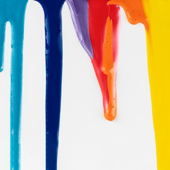 Dripping colorful paints on white background