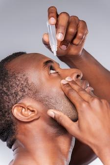 Капает ему в глаза глазные капли. вид сбоку молодого африканца, применяющего глазные капли, стоя на сером фоне