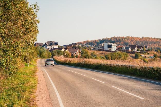 コテージのある美しい秋の丘の間を田舎道の秋の高速道路に沿ってドライブします。道路を急に曲がる。