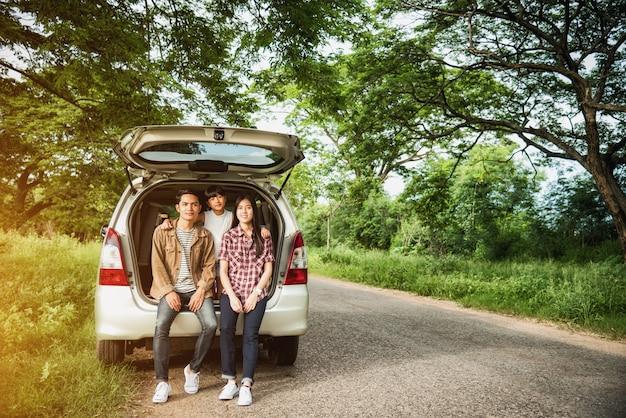 休暇の家族でドライブ。アジアの家族は自動車のオープントランクに座って幸せです