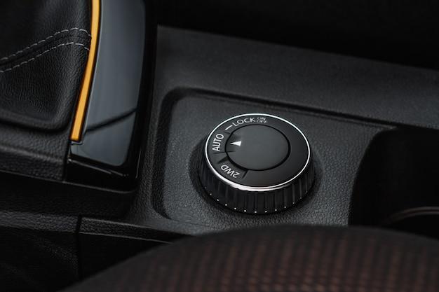 Кнопка выбора привода. рычаг акпп и переключение передач. интерьер автомобиля, вид крупным планом контроллера привода бездорожья. выбор полного привода. система выбора трансмиссии с полным приводом.