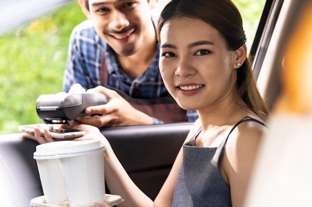 Азиатский клиент совершает бесконтактный мобильный платеж drive thru