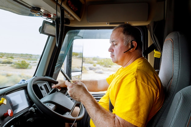 Driver on cabin on highway of smartphone in hand of man sitting behind the wheel of big modern truck vehicle