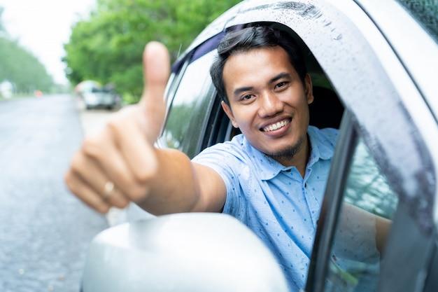 Водитель автомобиля показывает большой палец вверх на камеру