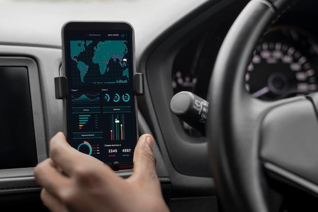 Autista che controlla il mercato azionario sul suo telefono mentre è in macchina