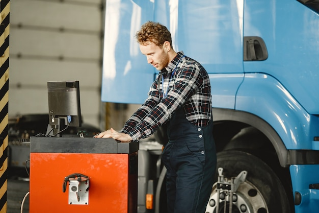 ドライバーが商品をチェックします。制服を着た男。ガレージのトラック