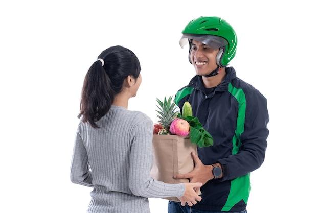 白で隔離された女性の顧客にオンライン注文を送信する食品とドライバー宅配便
