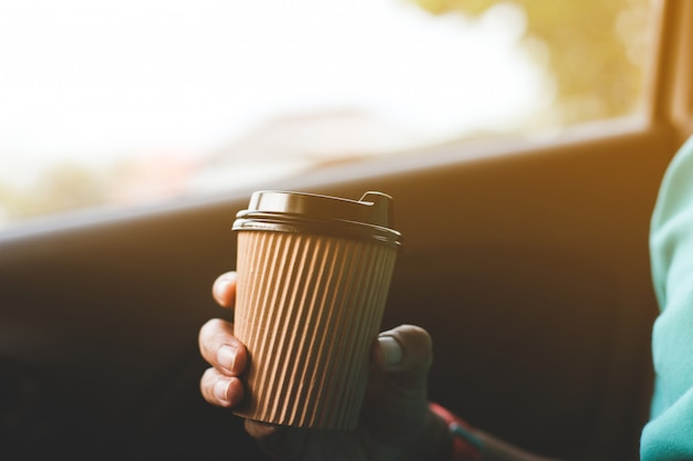 A driver drinking coffee in the car.
