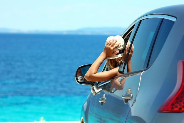 Девушка-водитель в шляпе в машине на море летом