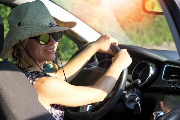 Девушка-водитель в солнцезащитных очках за рулем автомобиля на дороге