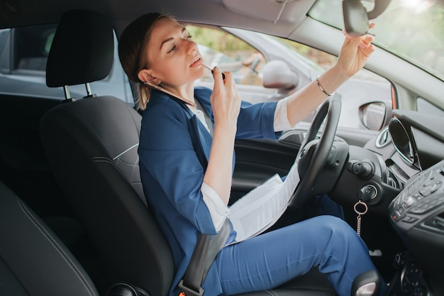 The driver going on the road, speaking on the phone, working with documents and doing a make up at the same time. businesswoman doing multiple tasks. multitasking business woman.