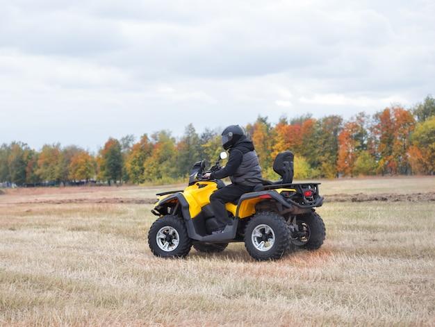 Driver in helmet on yellow quad bike on field