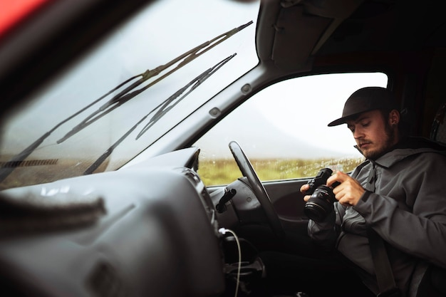 Driver holding a professional camera