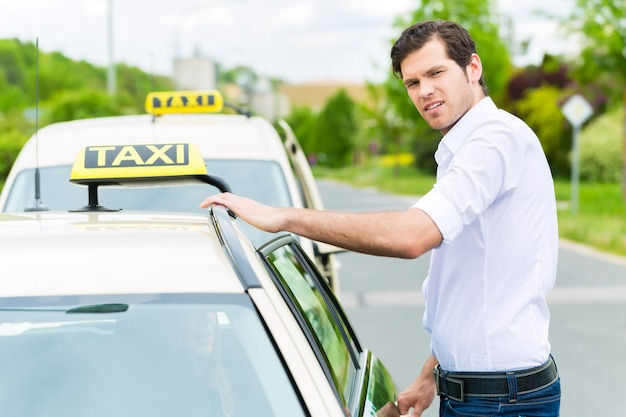 クライアントを待っているタクシーの前のドライバー