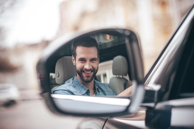 백미러에 있는 운전자. 차를 운전하는 동안 웃고 카메라를 바라보는 자신감 있는 청년