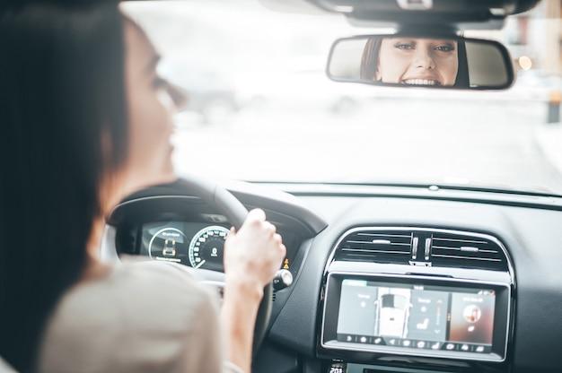 백미러에 있는 운전자. 백미러를 보고 차를 운전하는 동안 웃고 있는 캐주얼 차림의 매력적인 젊은 여성의 뒷모습