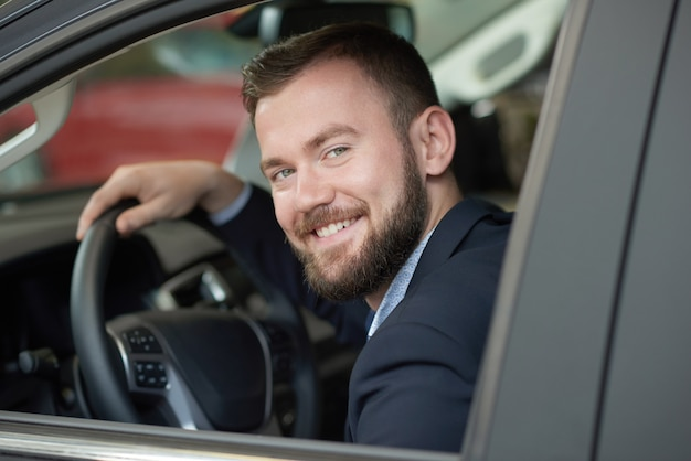 Driver looking at camera from car cabin and smiling.