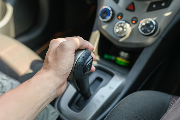 Driver male hand holding automatic gear shift
