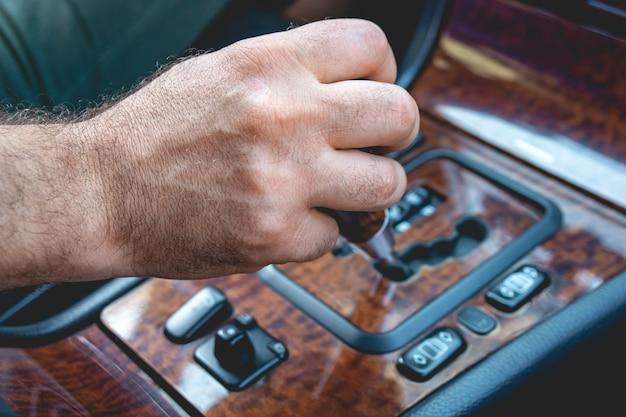 자동차에 자동 변속기를 들고 드라이버 남자 손입니다. 자동차의 자동 변속기 수준을 변경하는 남성 손.