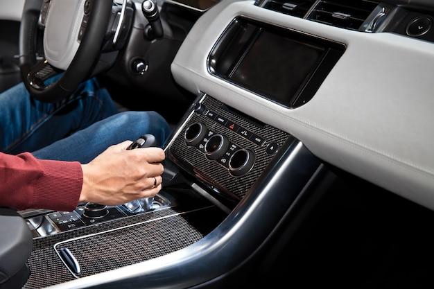車の中でオートマチックトランスミッションを持っているドライバーの男の手