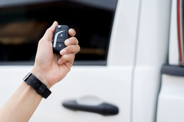 Driver man hand holding keyless of autonomous car for unlock via wireless technology