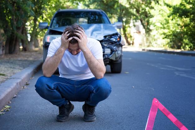自動車事故で大破した車の前にいる運転手。自動車事故の後、頭を抱えた怖い男。悲劇の車の衝突。危険な道路交通状況。