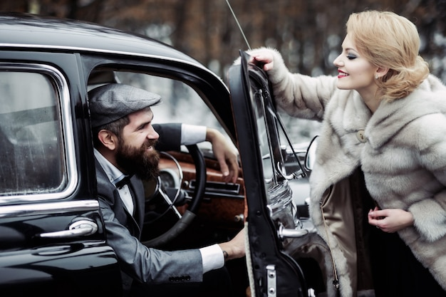 Driver man with woman in fur coat vintage couple at the black retro car