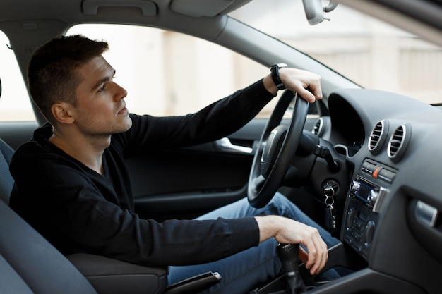 검은 티셔츠를 입은 남자의 운전자가 차에 앉아있다.