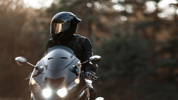 Водитель спортивного мотоцикла в защитном шлеме смотрит в сторону с включенными фарами. скопируйте место для вашего индивидуального текста