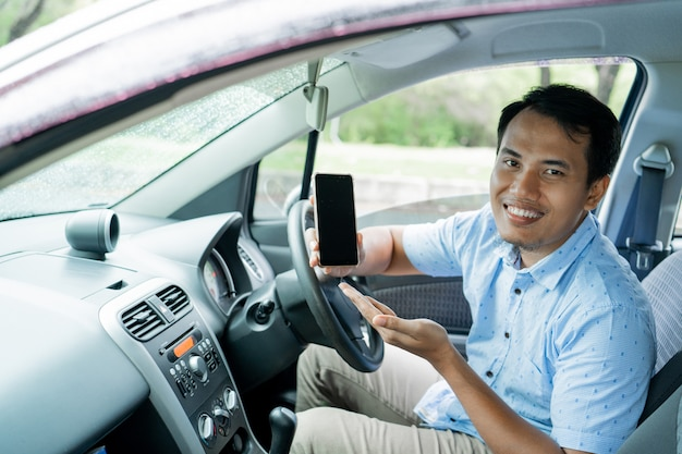 Driver online taxi in the car showing smartphone