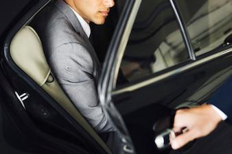 Водитель открывает дверь для бизнесмена